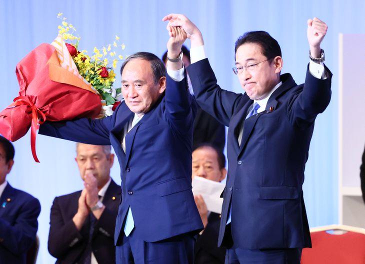 自民党総裁選挙で新総裁に選出され、菅義偉首相に花束を贈呈する岸田文雄氏(右)