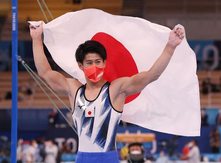 個人総合で金メダルを獲得し、日の丸を掲げて歓喜する橋本大輝=28日、有明体操競技場(川口良介撮影)
