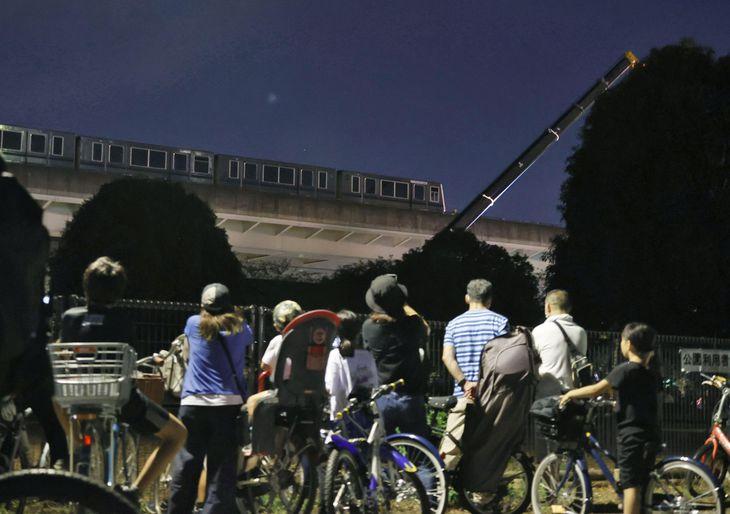 地震で脱線した新交通システム「日暮里・舎人ライナー」の車両の撤去作業と見守る人たち=8日夜、東京都足立区