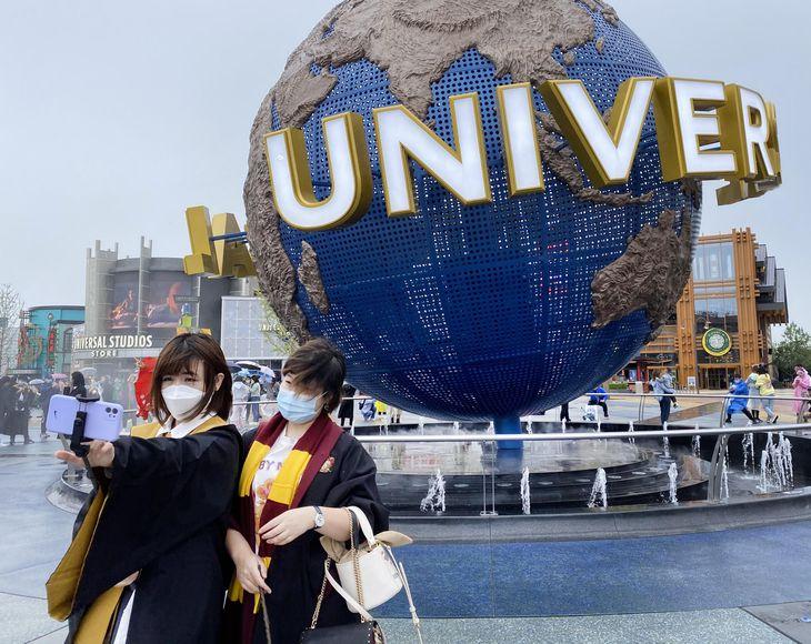 20日、北京市郊外の「ユニバーサル・スタジオ・北京」の前で記念写真を撮る来場者ら(三塚聖平撮影)