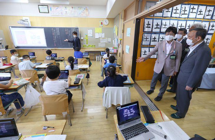 3年生のクラスでタブレットを活用した授業を視察し、松野泰一校長の説明を受ける菅義偉首相(右)=10日午前11時22分、東京都杉並区の区立天沼小学校(萩原悠久人撮影)