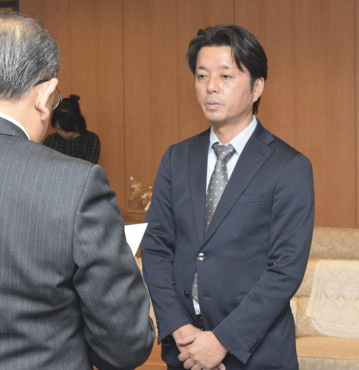 松本隆弘議長(左)から辞職勧告を言い渡される樽谷彰人県議=神戸市中央区