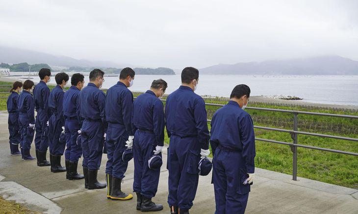 東日本大震災の津波で被災した高田松原の海に向かい黙とうする大船渡署の警察官ら=22日午前、岩手県陸前高田市