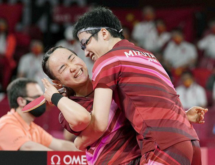 混合ダブルスで金メダルを獲得し、抱き合って喜ぶ水谷隼(右)と伊藤美誠=東京体育館