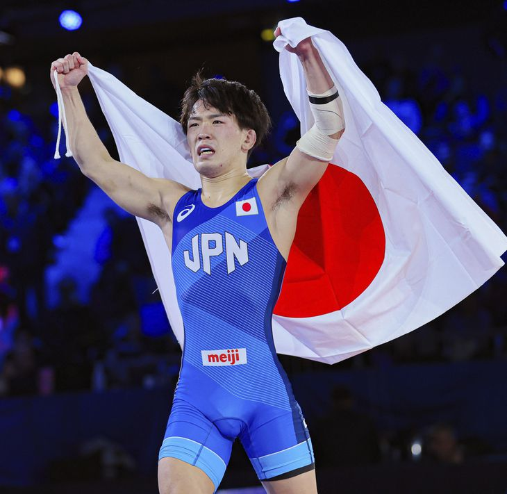 男子グレコローマンスタイル55キロ級で優勝し、日の丸を掲げる松井謙=オスロ(共同)