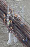 大和川に架かる近鉄南大阪線の橋脚が傾き、復旧作業する係員=25日午後(本社ヘリから)