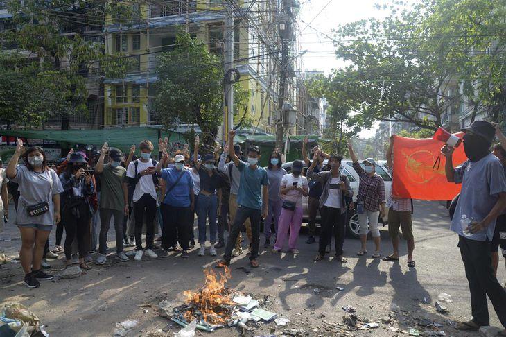 1日、ミャンマー・ヤンゴンで、国軍に抗議して憲法の冊子を焼くデモ参加者(AP)