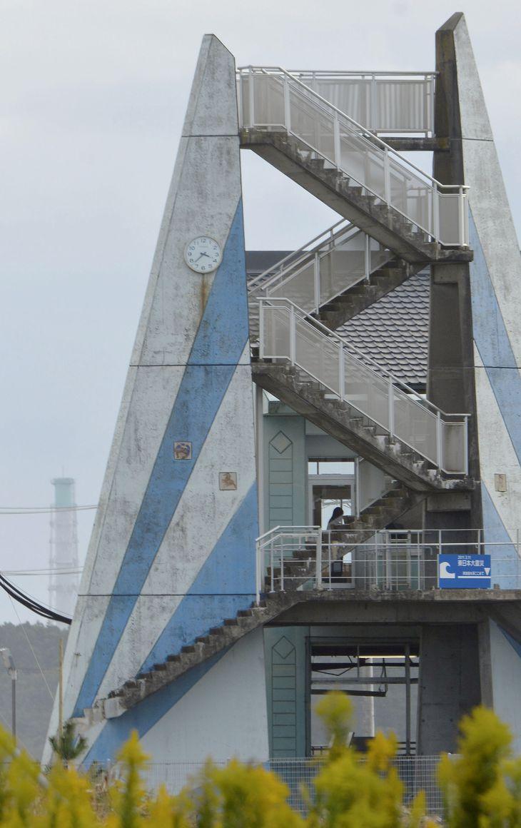 請戸小校舎の時計(左上)は津波に襲われた時刻で止まっている。左奥は東京電力福島第1原発の排気筒=7日午後、福島県浪江町