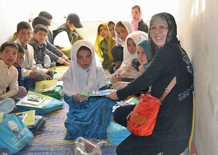 アフガニスタンの子供たちに文房具を配る中道貞子さん(右)=2011年(中道さん提供)