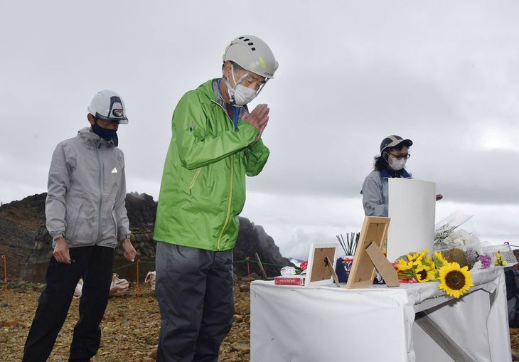 噴火後初めて御嶽山の「八丁ダルミ」を訪れ、手を合わせる丹羽隆文さん=26日(山びこの会提供)