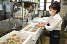 道の駅のレストランで作ったご飯などを箱詰めする職員=奈良県平群町