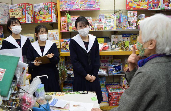 店主に取材するプール学院高校の生徒ら=大阪市生野区の生野本通中央商店街