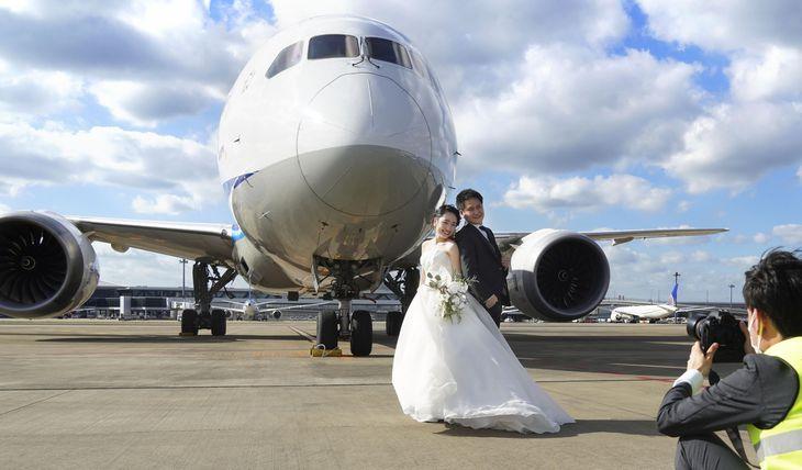 旅客機のすぐ近くで結婚の記念撮影に臨む角田敬さんとゆうかさん=11日午後、成田空港