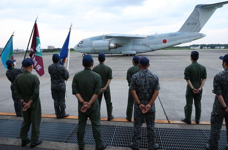【アフガニスタンに自衛隊機派遣】入間基地に駐機するC-2輸送機を見つめる航空自衛隊員ら=8月23日午後、航空自衛隊入間基地(川口良介撮影)
