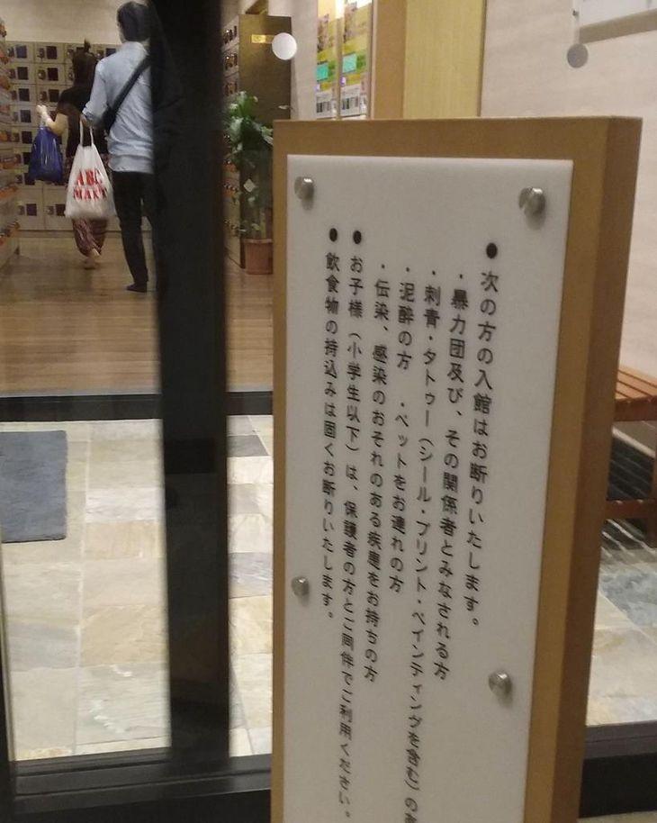 入れ墨、タトゥーを入れた客の入浴禁止を告知する、温浴施設の看板=10月2日、岡山市北区