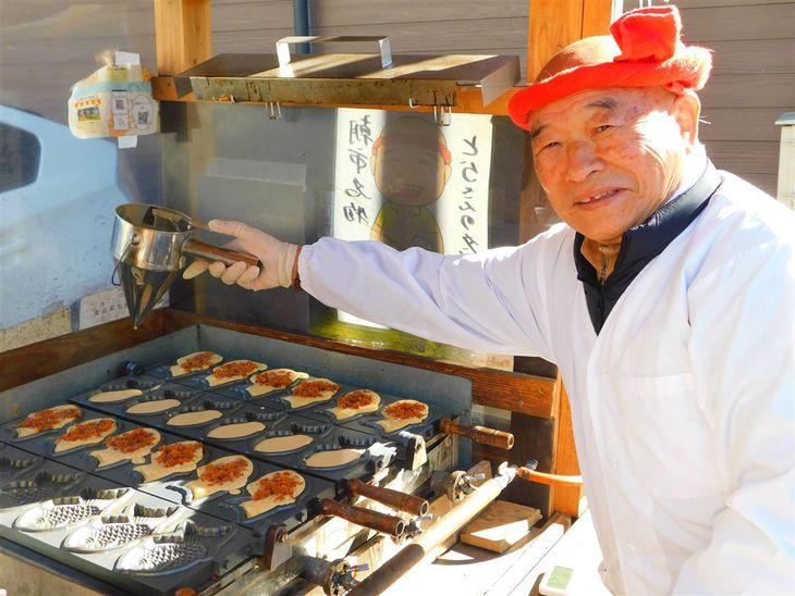 はちまきがトレードマークの江沢修さん。「タンタンたい焼き」は、朝市の名物の一つになっている=勝浦市(撮影のためにマスクを外しています)