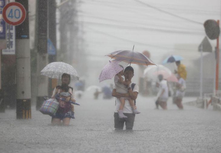 冠水した道路を歩く人たち=14日午前9時36分、福岡県久留米市