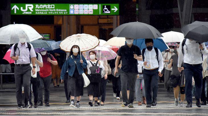 緊急事態宣言が解除。雨の中通勤する人たち=1日午前8時29分、JR東京駅前(酒巻俊介撮影)