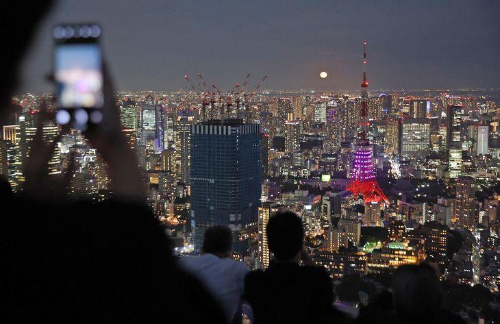 【中秋の名月2021】中秋の名月の満月と東京タワー(中央右)。六本木ヒルズスカイデッキでは写真撮影などをする人の姿がみられた=21日夜、東京都港区(佐藤徳昭撮影)